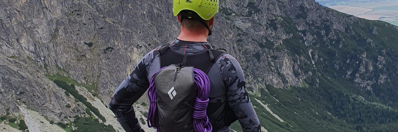 mężczyzna w kasku i z plecakiem tyłem stoi i patrzy na góryzy