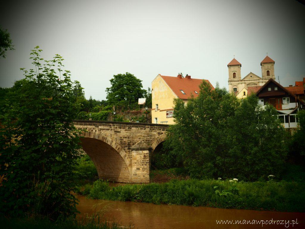 Rzeka, stary most, budynki ikościół woddali